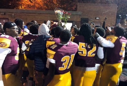 The Dunbar football team huddles together immediately following its victory over Patterson on Friday, Nov. 1.
