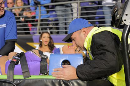A member of the medical staff reassures a Ravens cheerleader who was injured during an apparent fall during the third quarter of the game against the Tennessee Titans.