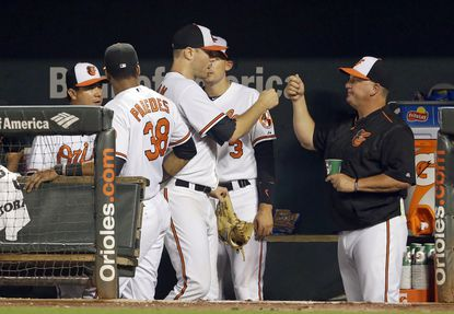 Orioles starting pitcher Chris Tillman, center, fist-bumps teammates in the dugout after being relieved in the ninth inning against the Atlanta Braves, Wednesday, July 29, 2015, in Baltimore.