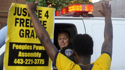 """Melvin Townes of West Baltimore stands with a """"Justice 4 Freddie Gray"""" sign in front of a police officer. Protesters gathered at McKeldin Square July 8, 2016, and then marched to protest the deaths of Alton Sterling and Philando Castile."""