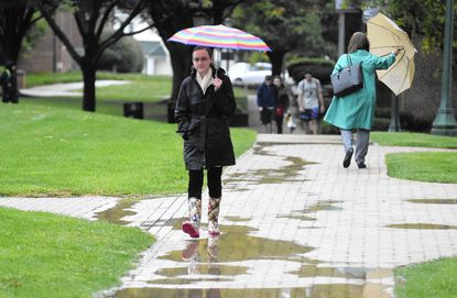 McDaniel College employee Andrea Briggs walks the campus grounds as rain falls in Westminster Thursday, Oct. 1.