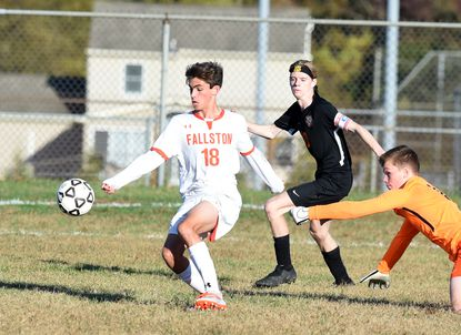Fallston's Devin Reddel stays on the loose ball as it gets away from Rising Sun goalie Austin Jacob and turns to score an easy goal during Wednesday afternoon's playoff match at Rising Sun.