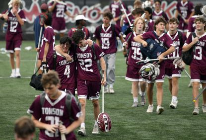 Towson teammates Cole Merashoff (4) and Will Derbyshire support each other as they react to their 7-6 loss to Urbana during the Class 3A boys lacrosse championship game at Loyola University's Ridley Athletic Complex on Friday, June 18, 2021.