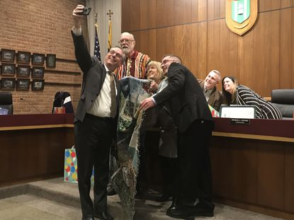 Michael Krantz, left, the director of administration for the Town of Bel Air who typically takes all the pictures at town meetings, takes a selfie with the commissioners after presenting the three leaving the board with a town blanket.