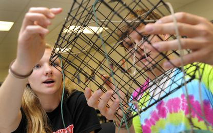Dana Lunkenheimer, left, and Luke Andraka, seniors at North County High School, designed a crab pot that will fall apart if left long enough instead of continuing to trap crabs.