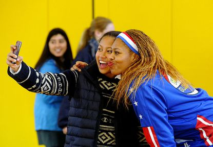 Bryn Mawr junior Irina Randrianarivelo takes a cell phone picture with Sweet J Ekworomadu of the Harlem Globetrotters at The Bryn Mawr School in Baltimore Thursday.