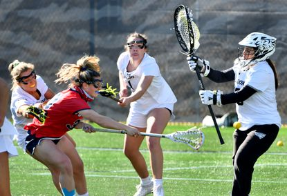 Stony Brook #30 Ally Kennedy scores the 10th goal past Towson goalkeeper #19 Lindsay Posner despite defensive efforts by Towson's #27 Olivia Malamphy, left, and #1 Rayna Deltuva. Stony Brook University women's lacrosse team beat Towson University, 10-8, at Tiger Field.