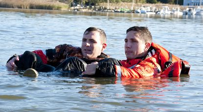 Coast Guard Seaman Kenneth Hunkus and Seaman James Potter buddy-up in the cold water of Fishing Creek in Annapolis during a safety demonstration Tuesday that encouraged boaters to prepare for cold-water survival.