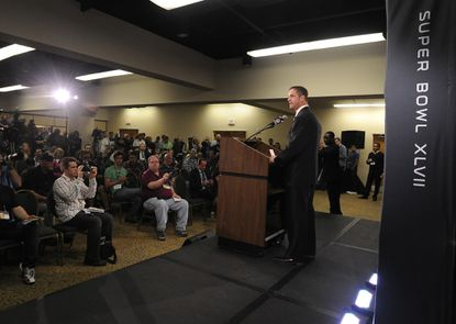 Ravens coach John Harbaugh talks to the media during a news conference after the team arrived in New Orleans.