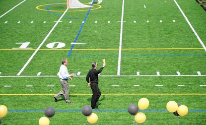 St. Margaret's Father Michael Schleupner blesses the new turf fields at The John Carroll School in Bel Air, as school President Richard O'Hara follows along with the holy water.