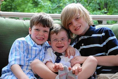 Keegan Turner, center, was a model at the Global Down Syndrome's Be Beautiful, Be Yourself gala in Washington, D.C. Here, he shares a moment with his brothers Atley, left, and Gavin.