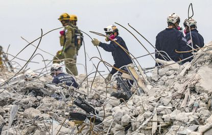 Search and rescue team members dig through the debris field of the 12-story oceanfront condo, Champlain Towers South along Collins Avenue in Surfside, Fla., on Wednesday, July 7, 2021. (Al Diaz/Miami Herald via AP)