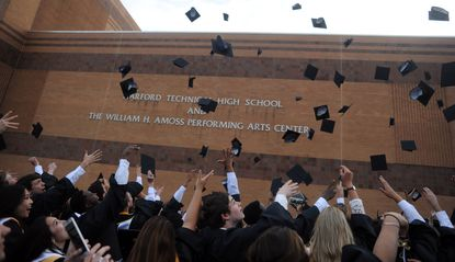 Graduates toss their caps outside the school following Harford Tech's commencement on Friday, June 5.