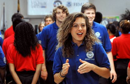 Erin Schoenbeck, 22, of Watertown, S.D., claps as she leaves the FEMA Corps induction ceremony at the Perryville Fire Department's Minker Hall.