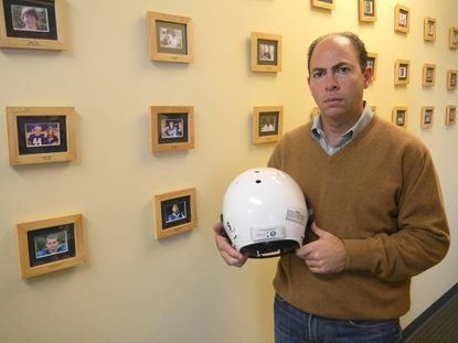 Greg Merill, co-founder of Brain Sentry, poses with a helmet in a hallway at the company's office, where pictures of 27 youth players who have died or been severely injured while playing football hang.