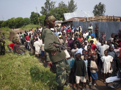 A rebel of the M23 group talks to residents after their troops entered the town of Rutshuru, near the Ugandan border on July 8, 2012.