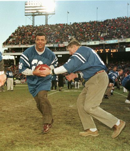 Legendary Colts quarterback Johnny Unitas hands off to former Colts running back Lydell Mitchell as the old-timers run one final play at Memorial Stadium in Baltimore on Sunday, Dec. 14, 1997. The ceremonial final play came at the conclusion of the final NFL game at the stadium. The Ravens defeated the Tennessee Oilers, 21-19.
