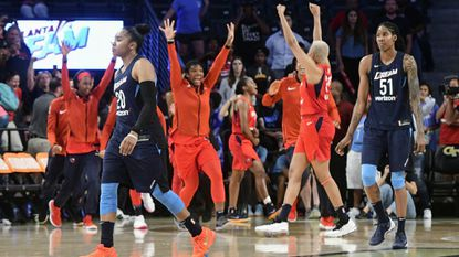Dream guard Alex Bentley (20) and forward Jessica Breland walk upcourt as Washington Mystics players celebrate behind them as Game 5 of the WNBA semifinals ends Tuesday, Sept. 4, 2018, in Atlanta. The Mystics won, 86-81, to advance to the finals for the first time.