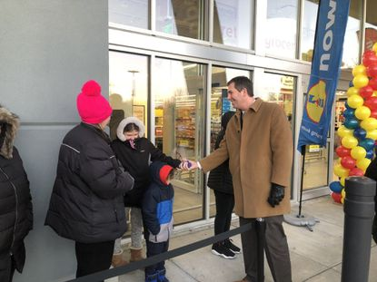 Baltimore County Executive Johnny Olszewski, Jr. greets customers waiting in line outside of Lidl's new Catonsville location Wednesday morning at 6026 Baltimore National Pike.