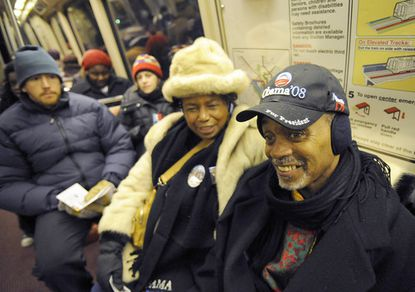 Diane Brown (center) and Melvin Collins (right) ride the Metro to Washington for the inauguration festivities.