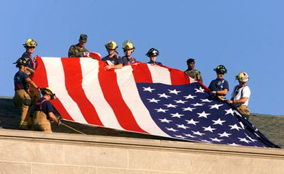 Rescue workers display the American flag on top of the Pentagon.