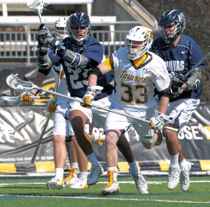 Towson's Tyler Mayes maintains possession of the ball while surrounded by Georgetown's Devon Lewis, left, and Chris Donovan on Feb. 27, 2016. Towson won, 10-7.