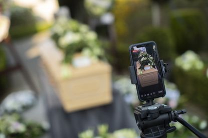 A smartphone broadcasts a live farewell ceremony at the Fontaine funeral home in Charleroi, Belgium, April 8, 2020. The deceased died due to the COVID-19 virus. (AP Photo/Francisco Seco)