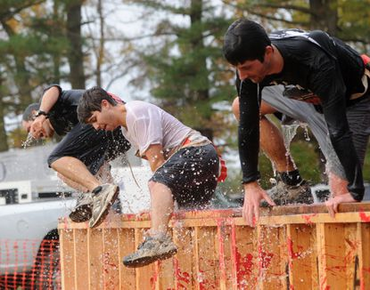 A few runners jump out of the Blood Bath obstacle near the finish line during the Zombie 5K at Camp Ramblewood Saturday.