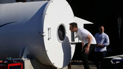 Elon Musk peeks inside a hyperloop track door in California. The Maryland Attorney General's Office has called into question the state's authority to grant permission to Tesla founder Elon Musk's tunneling startup to build several miles of tunnels for his high-speed Hyperloop.