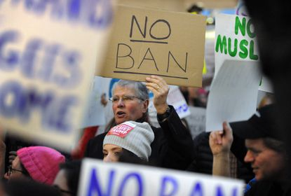 <p>Ian Menzies, of Annapolis, and his wife, not pictured, protest at BWI-Thurgood Marshall International Airport.</p>