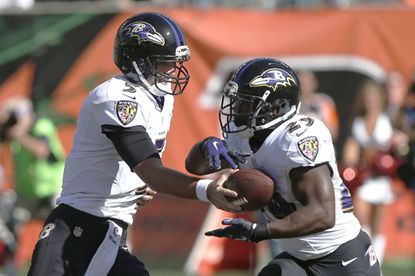 Ravens quarterback Joe Flacco hands the ball off to running back Justin Forsett during the first quarter against the Cincinnati Bengals at Paul Brown Stadium.