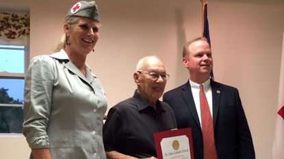 Beverley Rowe Stambaugh, executive director of the Western Maryland Chapter of the American Red Cross and Board member Andrew Heck honor Ted Cook, of Westminster, for his more than 40 years as a blood drive coordinator at St. John Catholic Church in Westminster.
