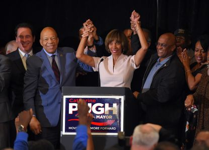 """On election night 2016, Rep. Elijah Cummings and then-City Council President Bernard C. """"Jack"""" Young hold up the arms of Catherine Pugh after she won the race to be Baltimore's mayor. Little did they know an ethics scandal would shorten her term."""