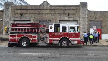 Baltimore City firefighters are seen in front of 439 E. Preston St., the Post Office Garage building that has been condemned.
