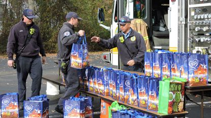 Nine Anne Arundel County firefighters delivered 106 meal bags to SPAN for its Thanksgiving meal distribution. Firefighters Corey MacRae (left to right), Jack Foster and Vincent Nichols help unload the food.
