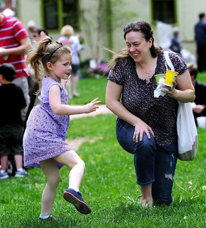 Grace Waller dances to swing music as her mother, Rachel Waller, looks on in front of the Westminster branch of the Carroll County Public Library during the 2014 Westminster Flower and Jazz Festival.