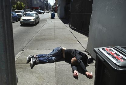 In this April 26, 2018, file photo, a likely substance abuser lies on the sidewalk beside a recyclable trash bin in San Francisco. (AP Photo/Ben Margot, File)