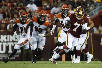 Washington Redskins quarterback Dwayne Haskins (7) scrambles away from Cincinnati Bengals defensive end Jordan Willis (75), defensive tackle Andrew Brown (93) and defensive tackle Renell Wren (95) during the first half of an NFL preseason football game Thursday, Aug. 15, 2019, in Landover.