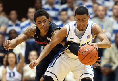 Terps guard Nick Faust, left, and Duke's Quinn Cook battle for a loose ball in the first half at Cameron Indoor Stadium.