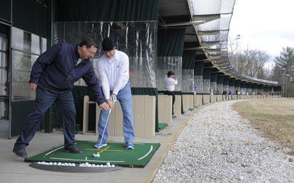 Jim Kardash of Arundel Golf Park gives a few golf tips to Chris Alderucci.