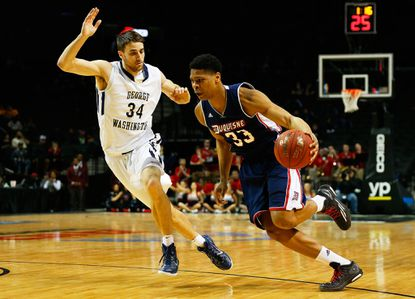 Duquesne'sL.G. Gill drives to the basket during the second round of the Atlantic 10 basketball tournament at Barclays Center on March 12, 2015 in New York, New York.