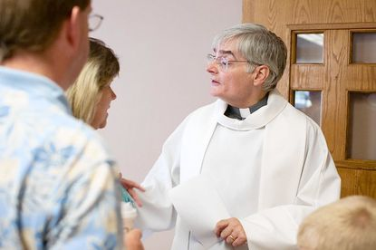"""Pastor Peter Smith, right, talks with members of the congregation at St. Charles of Brazil, an independent Catholic church that meets in Lansdowne, after services on July 8. On July 12 the church will show """"Our House,"""" a film that examines marriage for same-sex couples."""