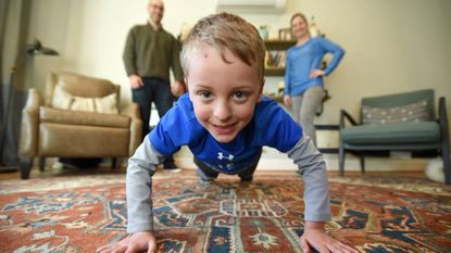 Six-year-old Drew Bove is joined by his parents Patrick and Britney Bove as he demonstrates his pushup technique at his home in Stoneleigh. He has raised more than $7,200 for the American Heart Association through a pushup campaign.