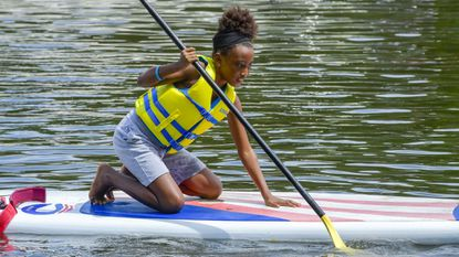 Mikiyah Sommerville tries out a paddleboard during Kids on the Creek, hosted by the Spa Creek Conservancy, last weekend at the Truxtun Park boat ramp in Annapolis.
