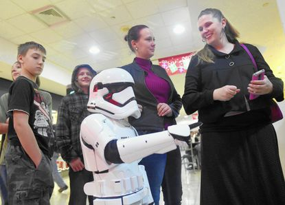 """Noah Johnson, 6, wears a full stormtrooper costume as he waits to enter the theater for the opening of """"Star Wars: The Force Awakens"""" with, from left, Justus Shupe, 11, his brother Peter Johnson, 11, Jennifer Shupe, and his mother Shannon Johnson outside Regal Cinemas Westminster 9 in Westminster TownMall Thursday, Dec. 17."""