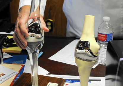 Surgeon John O'Hearn shows a traditional knee implant (left) as compared to the new, customized ConforMIS knee replacement (right), which uses 3D printing..