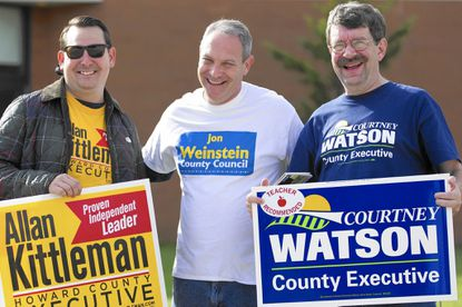 Brad Myers and Bill Neault, both of Elkridge, share a laugh with District 1 County Council candidate Jon Weinstein, center, outside Elkridge Elementary on Election Day.