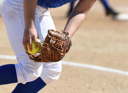 A softball pitcher delivers the pitch to the waiting batter.