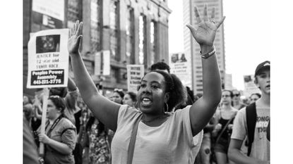 Aprotester marches downtown against police violence.