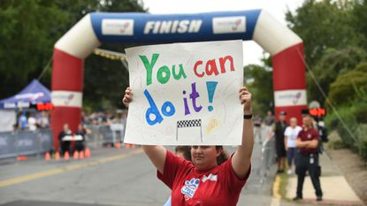 Beth Guidice holds a sign in support of the athletes competing during the Susquehanna River Running Festival on Saturday, Sept. 15.